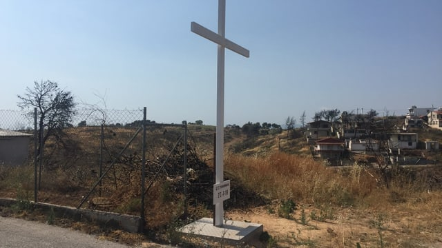 Ein grosses weisses Kreuz ausserhalb des Dorfes.