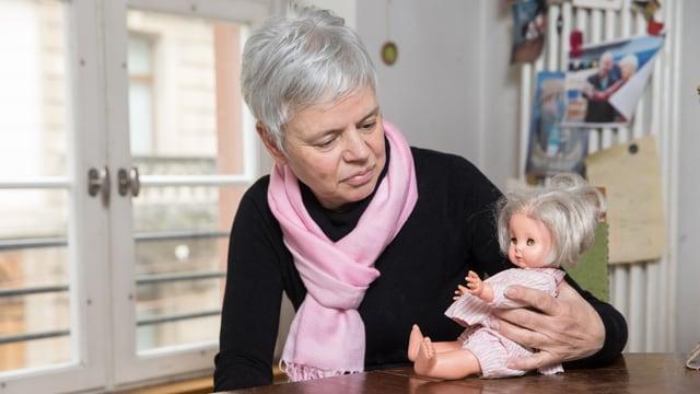 Eine Frau sitzt an einem Tisch. Sie schaut auf eine Puppe, die sie in der Hand hält.