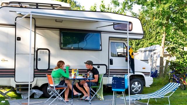 Zwei Camper sitzen vor ihrem Wohnwagen auf einem Campingplatz.