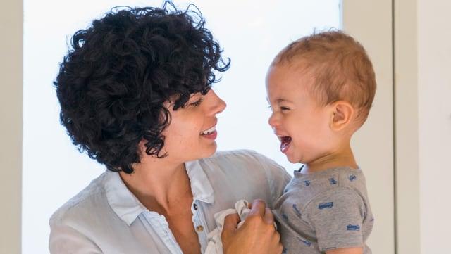 Eine Mutter schaut ihr Baby an. Es lacht.