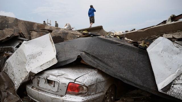 Ein Junge steht auf einem Trümmerhaufen, das Heck eines silbernen Autos schaut heraus.