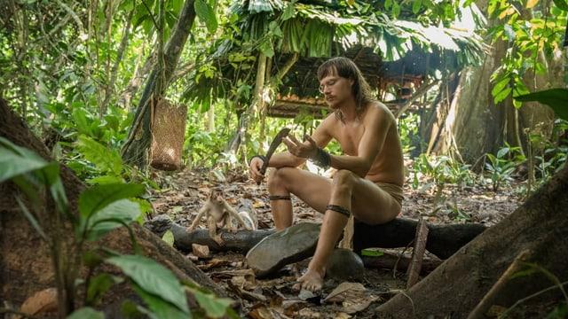 Ein halbnackter Mann sitzt im Urwald.