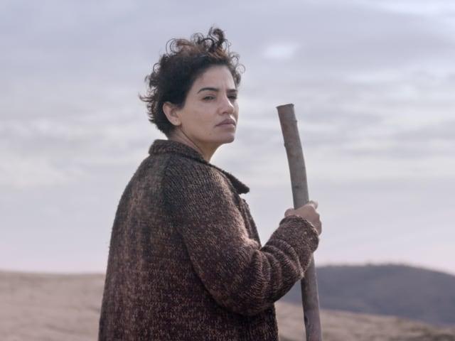 Eine junge Frau steht draussen und hält einen Stock in der Hand.
