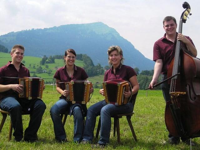 Ein Musikant und zwei Musikantinnen spielen Schwyzerörgeli, ein Musikant spielt Kontrabass. Die Formation sitzt auf einer grünen Wiese vor der Rigi.