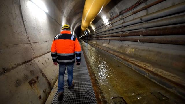 Mann in oranger Weste zu Fuss in einem Tunnel.