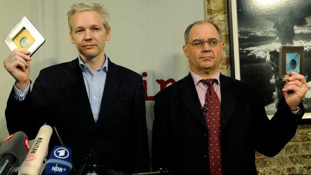 Zwei Männer mit je einer Daten-CD in der Hand, im Vordergrund Radiomikrofone