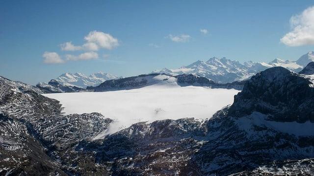 Blick auf eine Gletscherebene umgeben von Bergen.