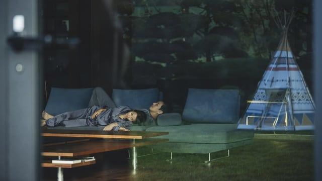 Ein Mann und eine Frau schlafen auf einem Sofa in einem geräumigen zimmer, im Hintergrund ein Tipizelt.