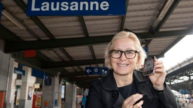 Pilloud lächelt mit einem Handy in der Hand in die Kamera, oberhalb von ihr das Bahnhof-Schild von Lausanne.