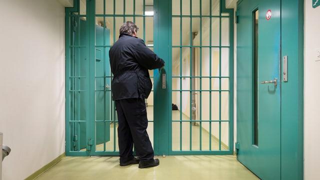 Aufseher in einem Gefängnis schliesst eine Gittertür ab
