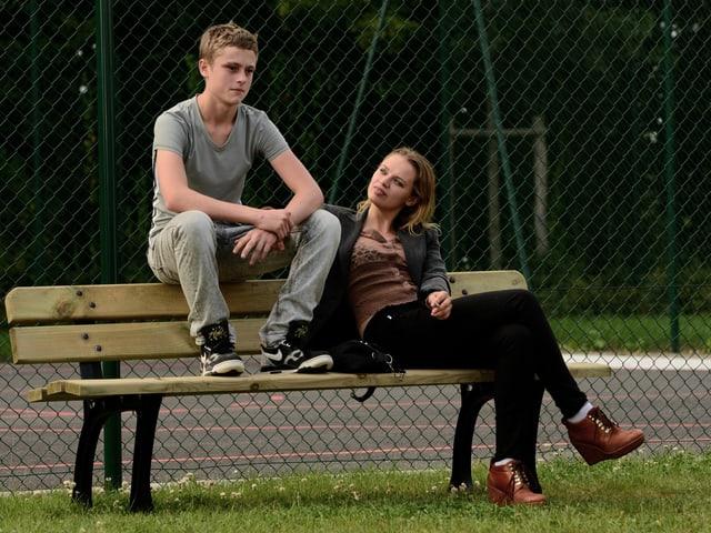 Junge sitzt auf der Lehne einer Bank, eine Frau sitzt auf der Bank.