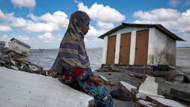 Ein Mädchen mit Kopftuch sitzt neben einem Haus, das zur Hälfte ins Meer gesunken ist.