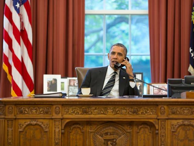 Barack Obama sitzt an einem Tisch und telefoniert.