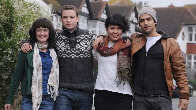 Vier Jugendliche die gemeinsame eine Strasse hinunterlaufen.