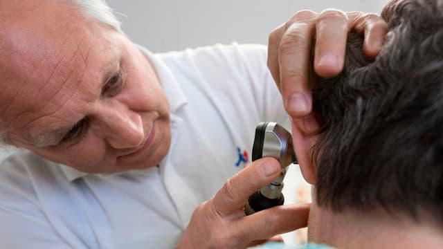 Ein Hausarzt untersucht das Ohr eines Patienten.