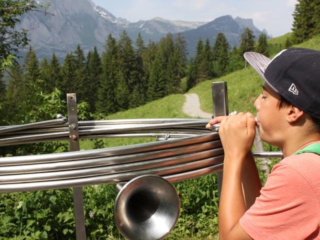 Ein Junge bläst in ein Horn, dahinter eine schöne Berglandschaft.