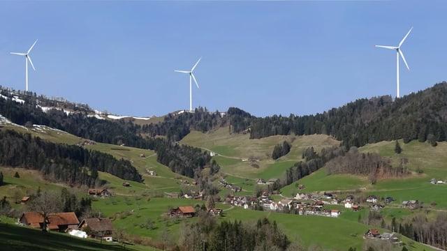 Drei Windräder stehen auf einer Bergkrete, im Vordergrund ein dorf in grüner Landschaft