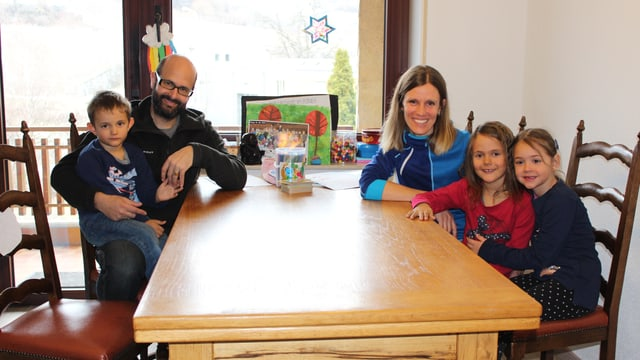 Eine Familie sitzt um den Tisch.