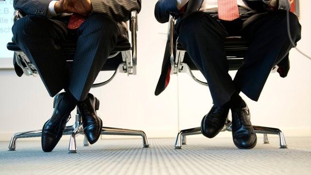 Zwei Männer in Anzügen sitzen auf Bürostühlen.