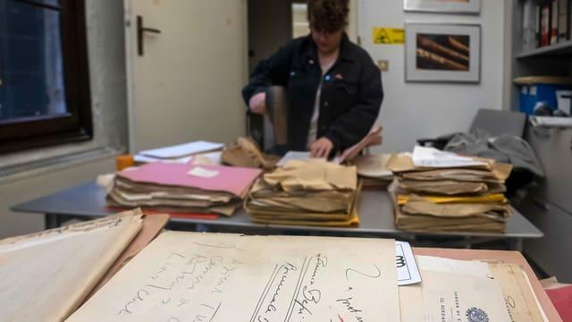Eine Frau trocknet alte Dokumente mit einem Föhn.