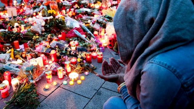 Eine junge Frau sitzt mit Kapuzze und gefalteten Händen nach dem Amoklauf in München vor Kerzen und Blumen.