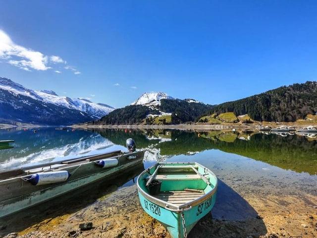 Blick auf einen Bergsee. Am Ufer liegt ein Ruderboot unter blauem Himmel.