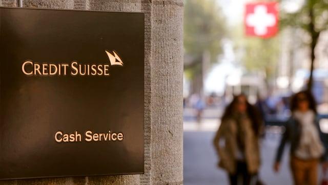 Ein Schild an der Bahnhofstrasse: «Credit Suisse Cash Service», im Hintergrund zwei Frauen und eine Schweizer Fahne.