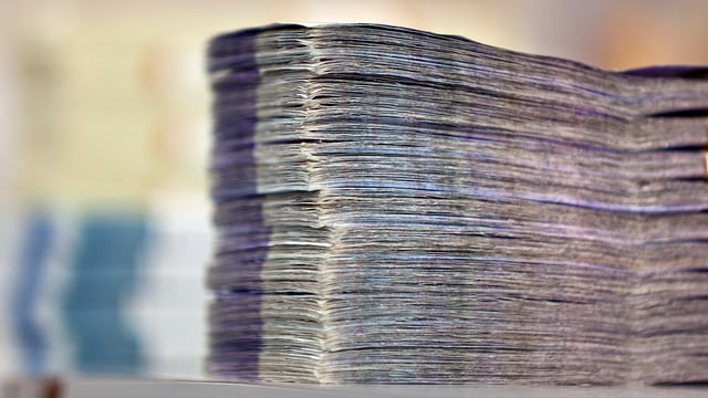 Bündel mit ganz vilen Tausendernoten. Das Geldbündel ist zusammen gebunden und man sieht es von der Seite.