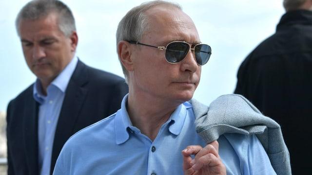 Putin mit Sonnenbrille in blauem Hemd.