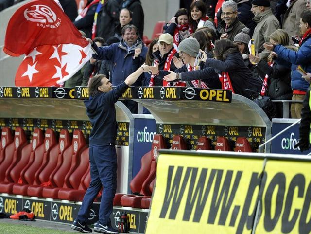 Ein Trainer klatscht seine Fans ab.