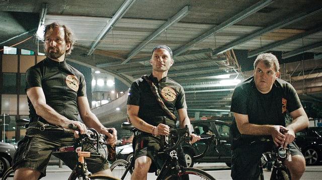 Drei Männer auf Fahrrädern.