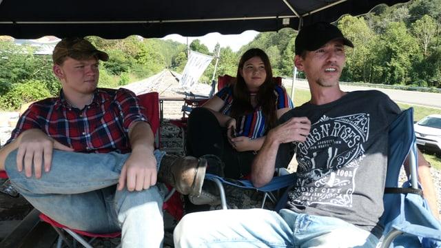 Zwei Männer und eine Frau sitzen unter einem Zelt