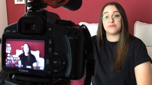 Eine Frau sitzt hinter einer Kamera.
