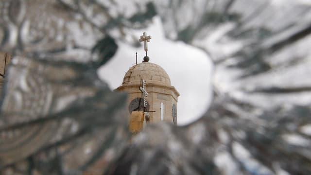 Blick durch eine kaputte Fensterscheibe auf eine Kirche in Syrien.