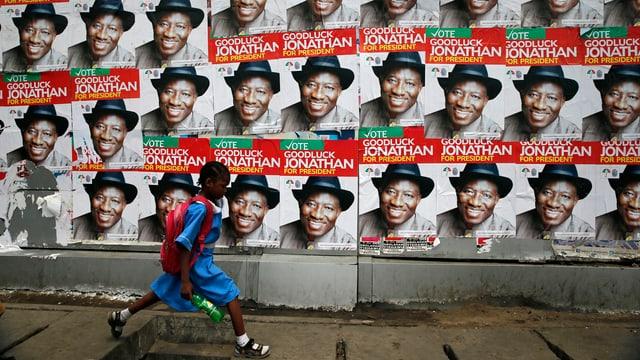 Ein Mädchen läuft vor einer Wand mit Wahlplakaten vorbei.