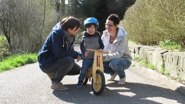 Zwei Frauen und ein Bube auf einem Laufrad