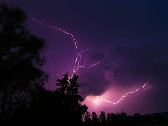 Blitze zücken am Nachhimmel und erleuchten diesen violett.