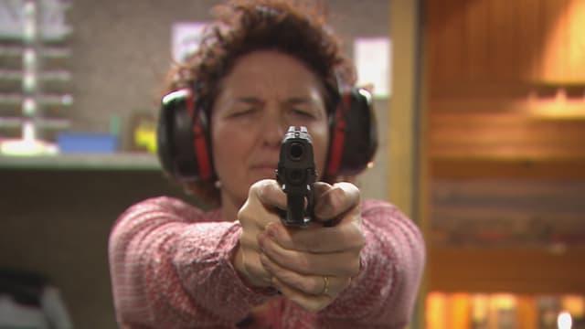 Frau mit Pistole im Schiesskeller.