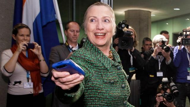 Hillary Clinton mit einem Smartphone in der Hand.