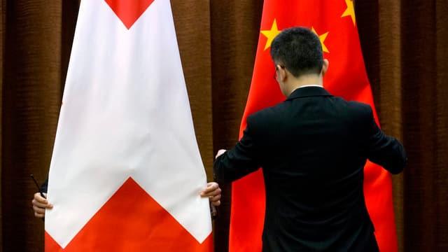 Zwei Personen rücken die Schweizer und die chinesische Flagge zurecht