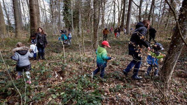 Viele Kinder und einige Eltern laufen auf der Eiersuche in einem Wald umher