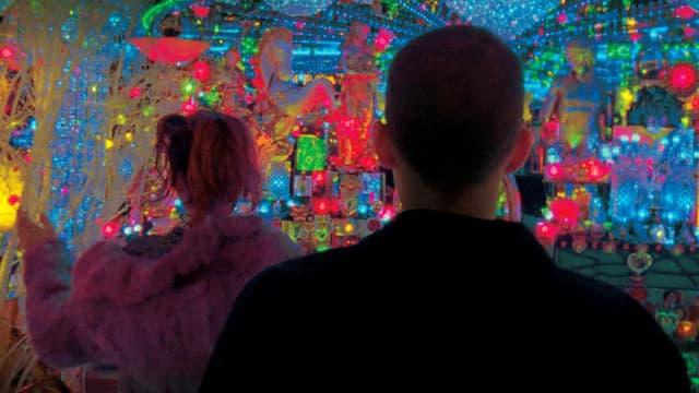 Zwei Menschen in einem Raum mit farbigen Lichtern.