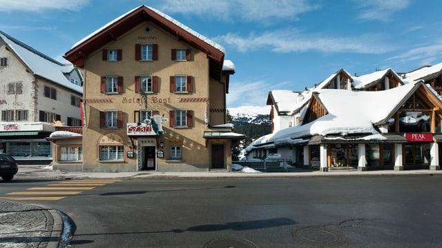 Platz in Lenzerheide. Häuser mit Schnee auf dem Dach. Schwarze Strasse.