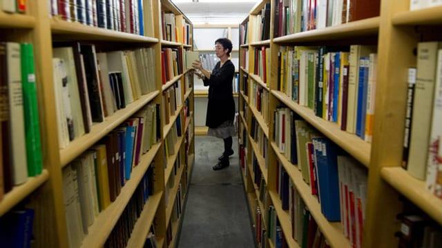 Zwei Gestelle mit Büchern, dazwischen eine Frau.
