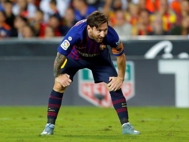 Lionel Messi steht in gebückter Haltung auf dem Rasen.
