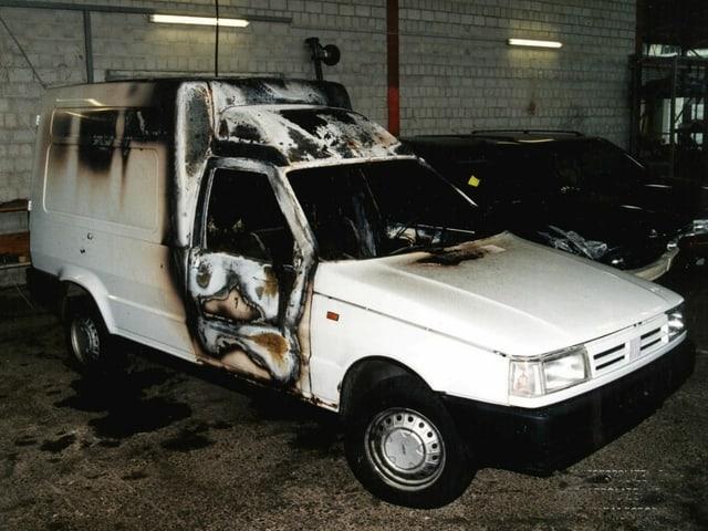 Ausgebrannter Lieferwagen in einer Garage.
