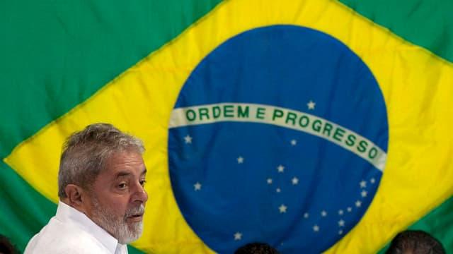 Lula da Silva vor der brasilianischen Flagge.