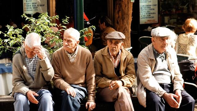 Vier ältere Männer sitzen nebeneinander an der Sonne.