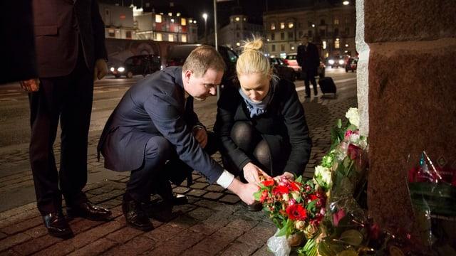 Eine Frau und ein Mann gehen in die Knie, um Kerzen anzuzünden. Daneben stehen ein paar Blumen.