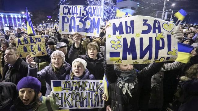 Hunderte Frauen, Kinder und Männer skandieren sichtbar Parolen, in den Händen halten sie Plakate auf denen Slogans aufgemalt sind.